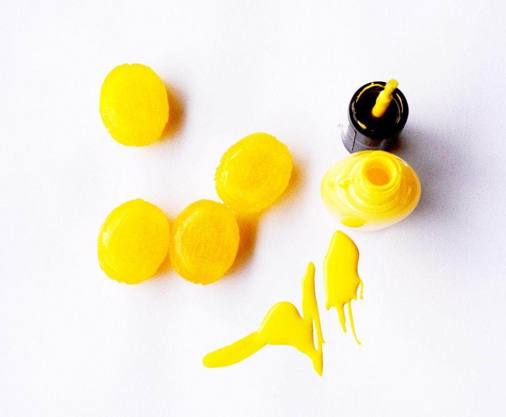 Auf dem Bild ist gelber Nagellack zu sehen.