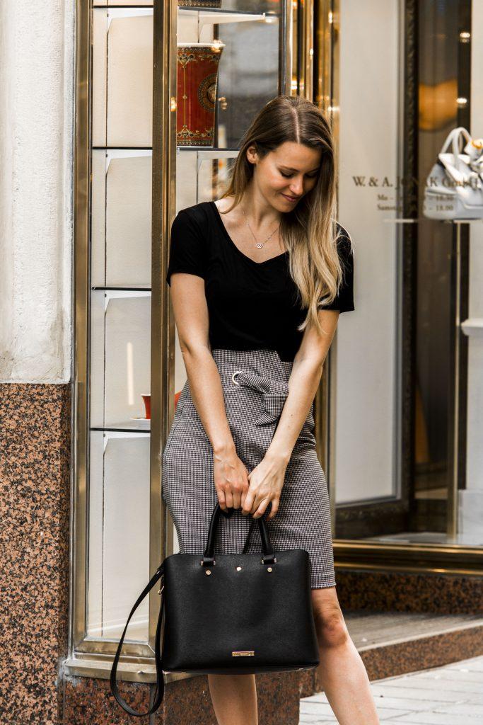 Auf dem Bild ist eine Frau in einem Wickelrock und einer schwarzen Tasche zu sehen.
