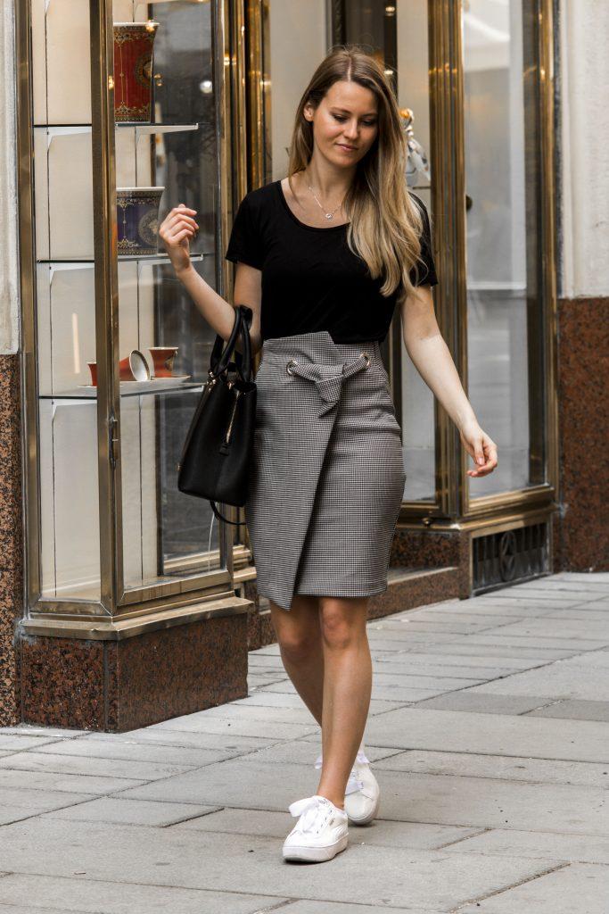 Auf dem Bild ist eine Frau in Rock und schwarzem T-Shirt und Sneakers zu sehen.