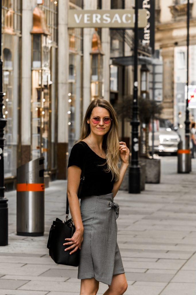 Auf dem Bild ist eine blonde Frau mit rosa Sonnenbrille zu sehen.