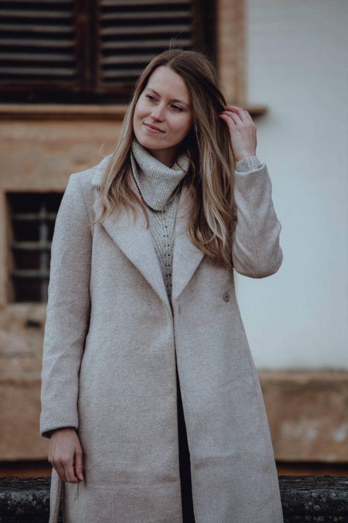 Outfit mit Rollkragen Pulllover und beigem Mantel. Halbtotale