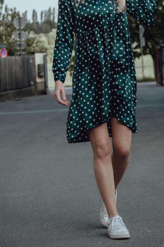 Detailaufnahme von gruenem Kleid mit Polkadots und dazu weiße Sneaker